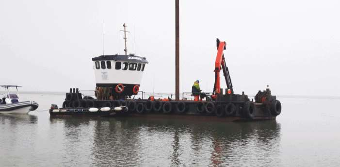 A 'Jumbo spud leg' barge is being used to strengthen 4km of boat moorings on Keyhaven River