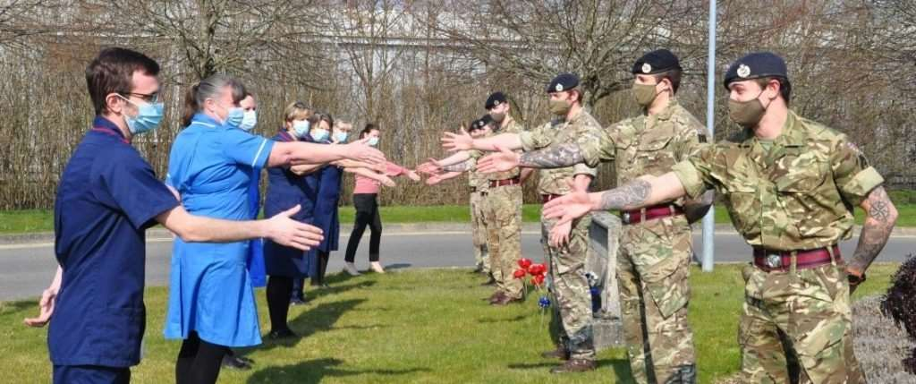 A socially distanced handshake between Lymington hospital staff and departing soldiers